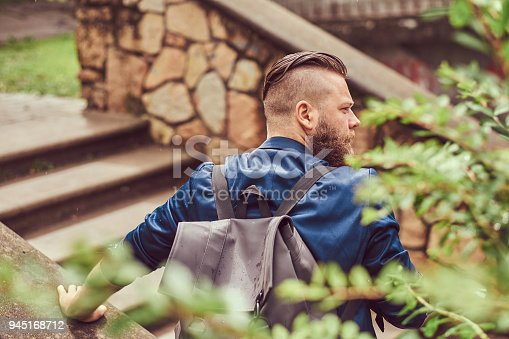 istock Back view portrait of a bearded male with a haircut dressed in casual clothes with a backpack, sitting in a city park 945168712