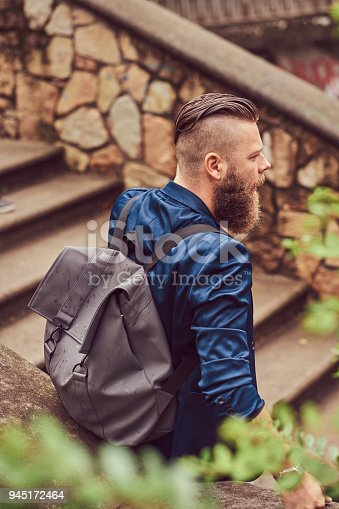 istock Back view portrait of a bearded male with a haircut dressed in casual clothes with a backpack, sitting in a city park 945172464