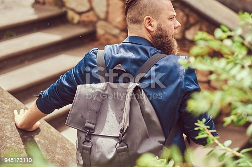 istock Back view portrait of a bearded male with a haircut dressed in casual clothes with a backpack, sitting in a city park 945173110