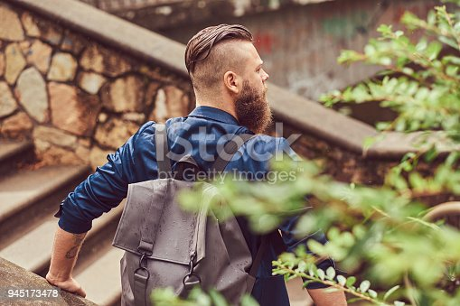 istock Back view portrait of a bearded male with a haircut dressed in casual clothes with a backpack, sitting in a city park 945173478