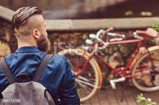 istock Back view portrait of a bearded male with a haircut dressed in casual clothes with a backpack, sitting in a city park 945173700