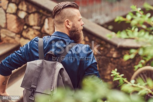 istock Back view portrait of a bearded male with a haircut dressed in casual clothes with a backpack, sitting in a city park 945174030