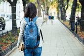 バックのポートレートを歩いて女性の学生