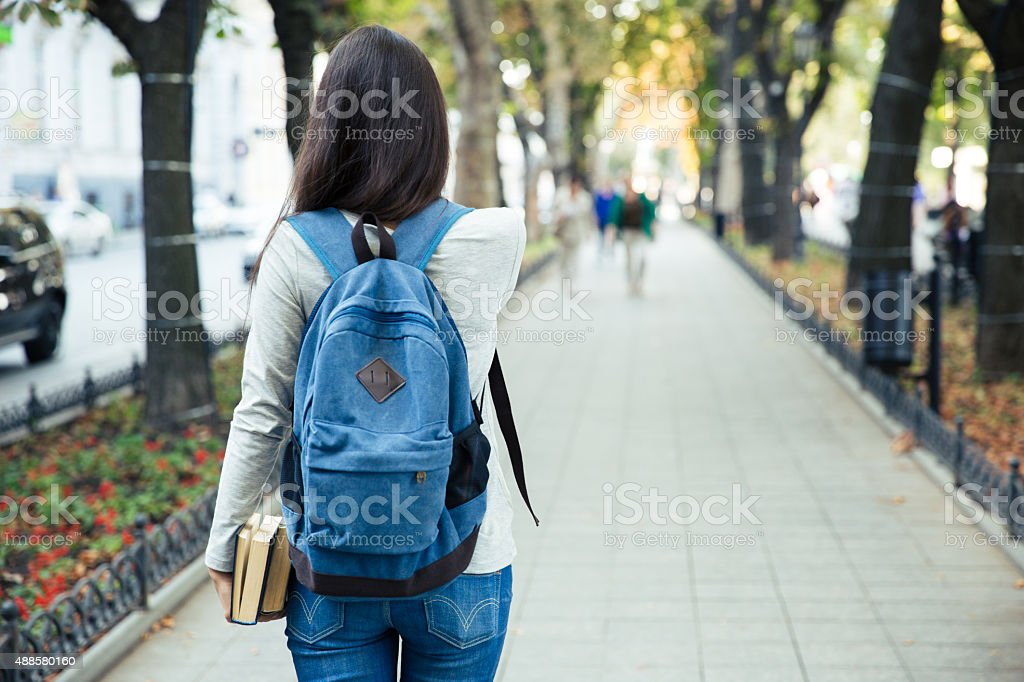 Back view portrait of a female student walking stock photo