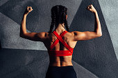 istock Back view portrait of a fitness woman showing biceps 905420704