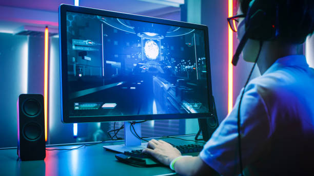 back view shot of professional gamer playing in first-person shooter online video game on his personal computer. he's talking with his team through headset. room lit by neon lights in retro arcade style. cyber sport championship. - desktop pc stock pictures, royalty-free photos & images