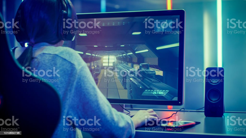 Back View Shot of the Beautiful Professional Gamer Girl Playing in Online First-Person Shooter Online Video Game on Her Personal Computer. Casual Cute Geek Girl Wearing Headset. Dark Room Suddenly Lit by Neon Lights in Retro Arcade Style. stock photo