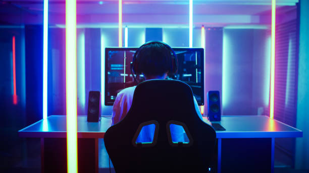 Back View Shot of the Beautiful Professional Gamer Girl Putting on Headset and Starts Playing Online Video Game on Her Personal Computer. Cute Casual Geek Girl. Room Lit by Neon Lamps in Retro Arcade Style. stock photo
