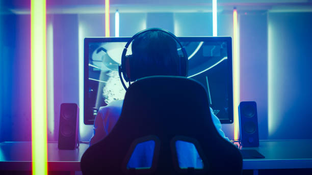back view shot of the professional gamer playing in first-person shooter online video game on his personal computer. room lit by neon lights in retro arcade style. online cyber e-sport internet championship. - esports stock photos and pictures