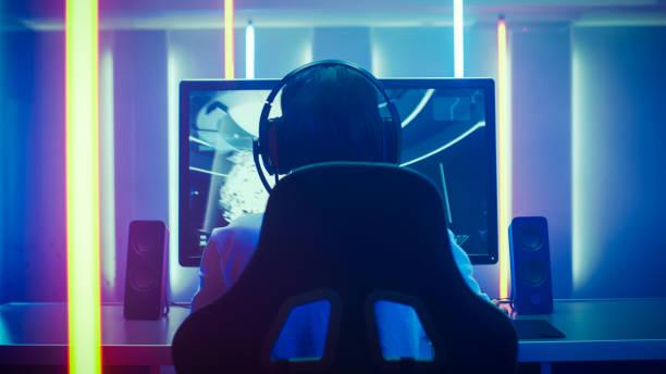 Rückansicht Schuss das professionelle Gamer spielen in First-Person-Shooter Online-Videospiel auf seinem persönlichen Computer. Zimmer, beleuchtet von Neonröhren im Retro-Arcade-Stil. Online-Cyber-e-Sport-Internet-Meisterschaft. – Foto