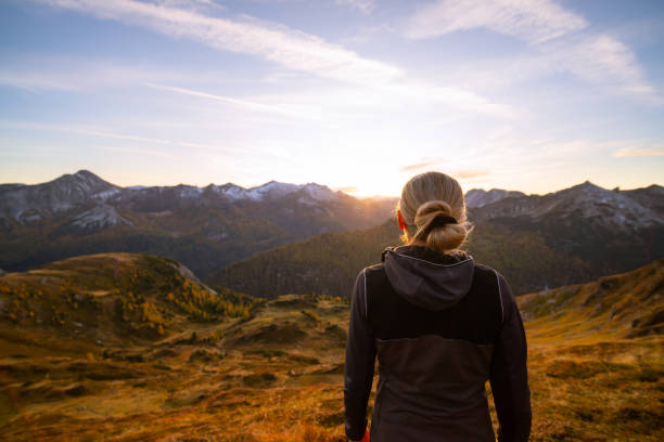 back view sporty woman watching sunset in mountains in autumn stock photo