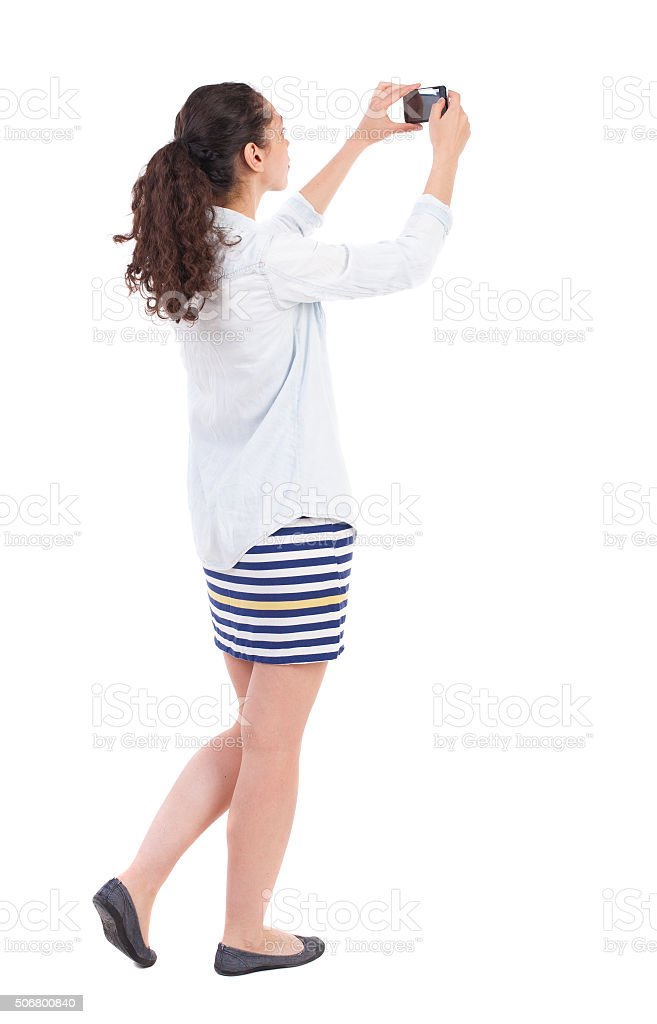 back view standing curly woman with mobile phone in hands stock photo