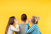 istock back view teenage women whisper secrets man yellow 1079671492
