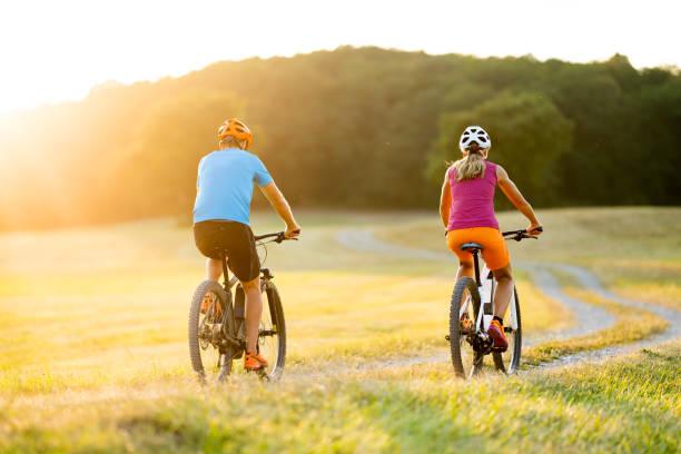 Rücken zwei Mountainbiker auf e-Bikes im Sommersonnenschein ansehen – Foto