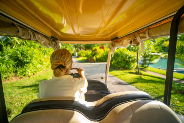 back view woman driving golf cart on tropical island stock photo