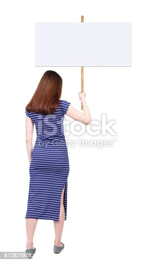 istock Back view woman showing sign board. 612821978