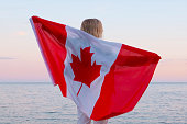 Back view woman waving national canada flag outdoors ocean sea sunset at summer - Canada day, country, patriotism, independence day 1th july