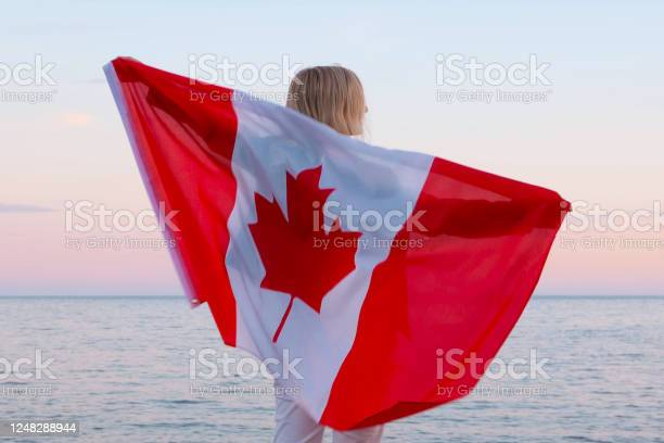 Photo of Back view woman waving national canada flag outdoors ocean sea sunset at summer - Canada day, country, patriotism, independence day 1th july