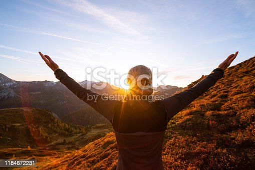 freedom, happiness, closeness to nature, rear view upper body woman with outstretched arms standing high up on alpine mountain pasture enjoying sunset over mountain range in autumn, star shapped sun