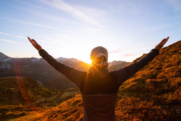back view woman with arms wide open in mountain sunset stock photo