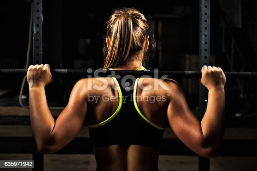 istock Back view young adult girl doing barbell squats 635971942