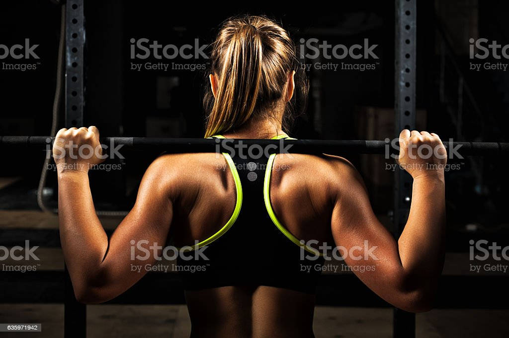 Back view young adult girl doing barbell squats - foto de stock