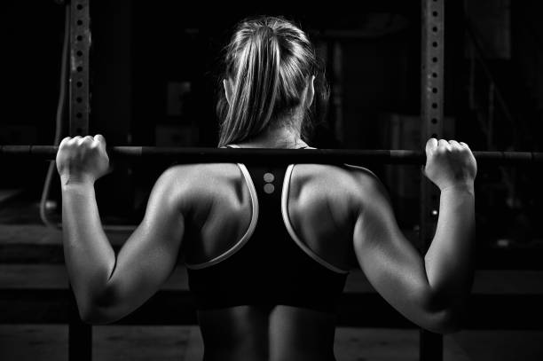 back view young female doing barbell squats in gym - pesistica foto e immagini stock