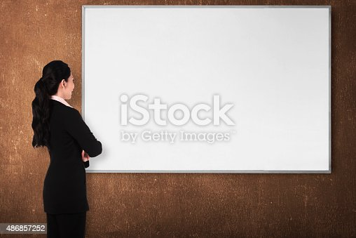 istock Back view young woman with white board 486857252
