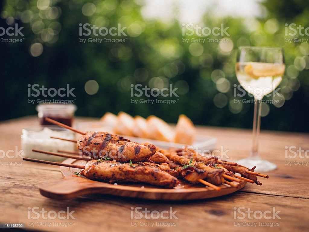 Back yard barbecue meal with chicken and white wine stock photo