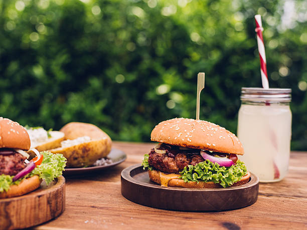 Back yard table with gourmet cheese burgers with summer beverage stock photo