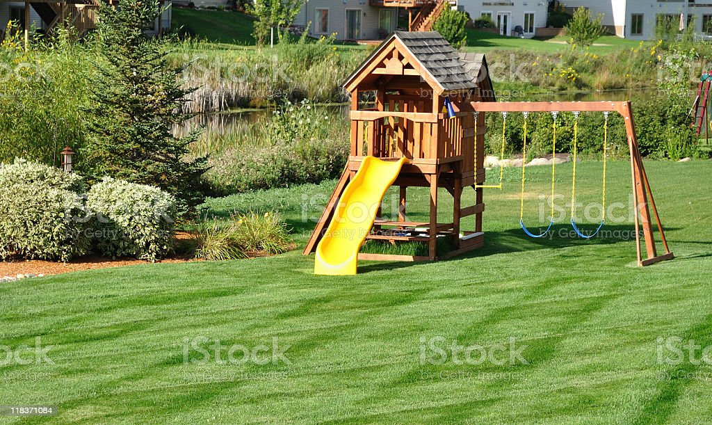 Back yard wooden play set surrounded by greenery stock photo