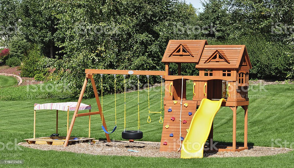 A back yard wooden swing set placed in a garden stock photo
