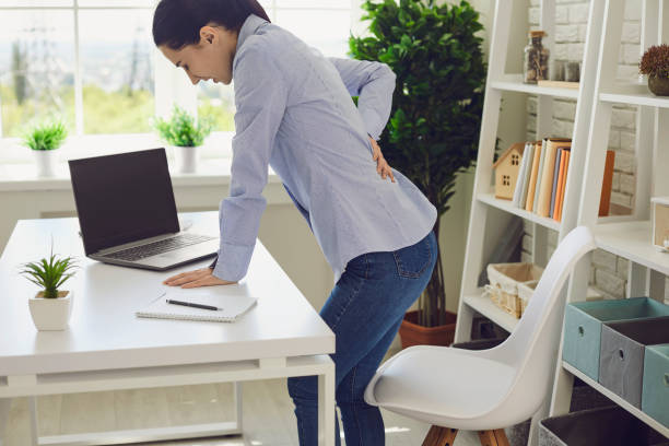 Backache. Woman suffering from back pain at workplace. stock photo