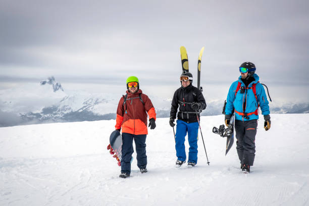 Backcountry Skier and Snowboarders on Mountain Summit stock photo