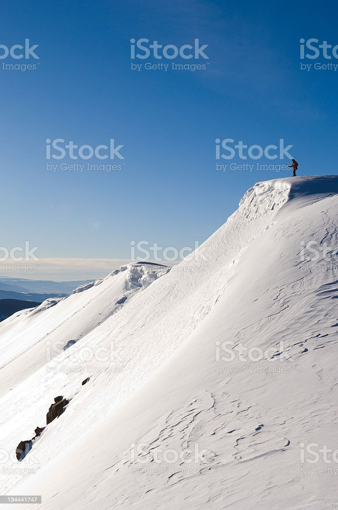 Backcountry Skier Mountaineer Standing on Corniced Mountain Ridge stock photo