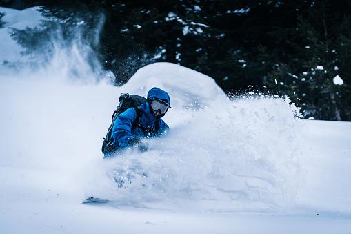Backcountry snowboarder descends mountain