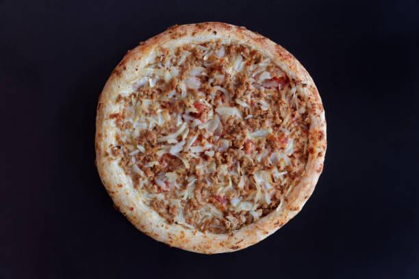 Backed tuna pizza on black background stock photo