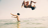 Woman doing a backflip off man's shoulders into the sea.