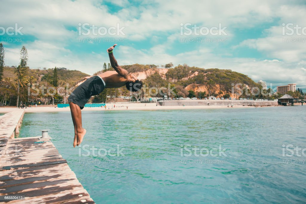 Backflip Pacific Islander jumping into the Water Noumea Beach New Caledonia royalty-free stock photo