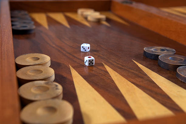 backgammon board in polished wood with die centrally placed - backgammon stock pictures, royalty-free photos & images