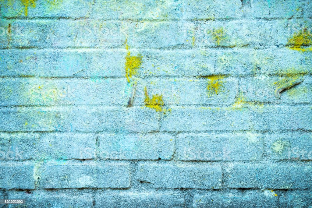 Background And Wallpaper Or Texture Of A Blue Brick Wall With Stains Yellow Paint Royalty