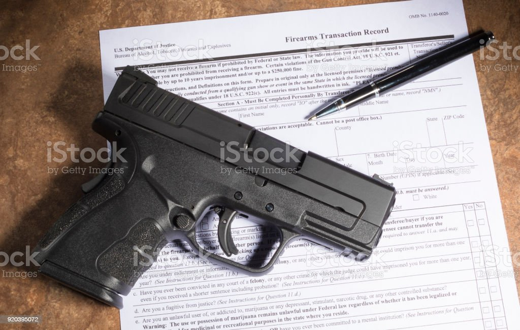 Background check for a gun purchase with a handgun Polymer handgun and paperwork to purchase it on a beige counter Backgrounds Stock Photo