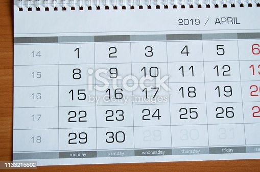 1027407218 istock photo Background dates on the calendar page April 2019, on a wooden table 1133215502