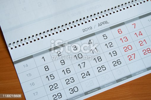 1027407218 istock photo Background dates on the calendar page April 2019, on a wooden table 1133215509
