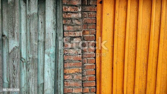 Background fence summer, autumn wooden planks brickwork with yellow wooden boards, brightly orange background. In summer city.