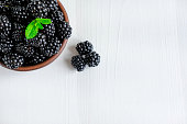 Background for a banner with blackberry berries on a light wooden background. Close-up photo of blackberries with copy space and mint leaves