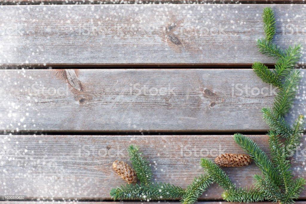 Fond pour Noël et nouvel an des planches avec une branche d'épinette avec des cônes et des sauts de neige sur le bord - Photo