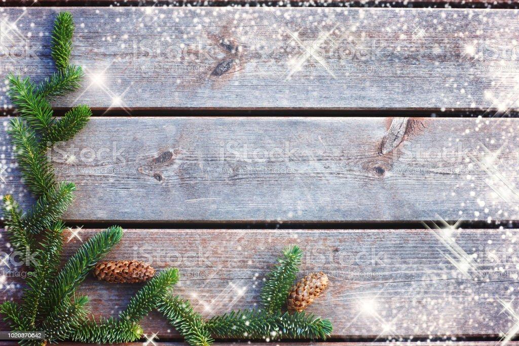 Fond pour Noël et nouvel an des planches avec une branche d'épinette avec les cônes et les étoiles brillaient - Photo