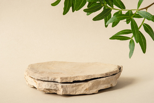 Background for cosmetic products of natural beige color. Stone podium with green leaves. Front view.
