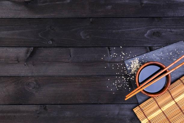 fond pour les sushis. natte de bambou et de sauce de soja sur la table en bois noir. vue de dessus avec l'espace de copie - cuisine asiatique photos et images de collection